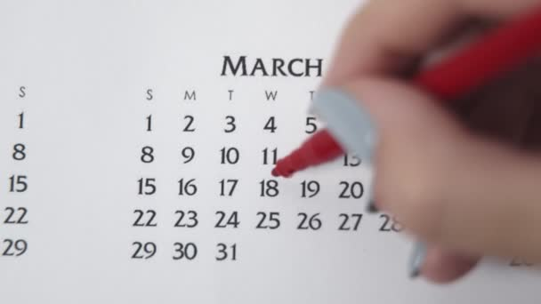 Female hand circle day in calendar date with a red marker. Business Basics Wall Calendar Planner and Organizer. MARCH 18th