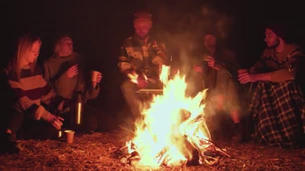 Piknik mladých lidí s ohněm v lese ve večerních hodinách. Veselí přátelé pijí horký čaj a mluví