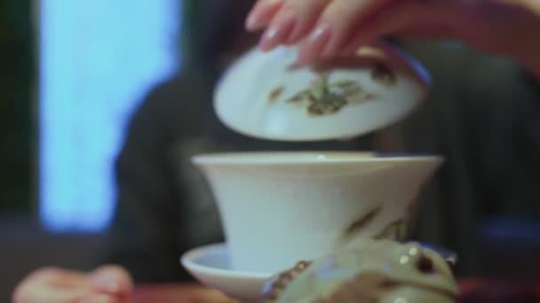 Vaření čínského čaje na čajové desce. Žena nalévá čaj z konvice do šálku a pije ho