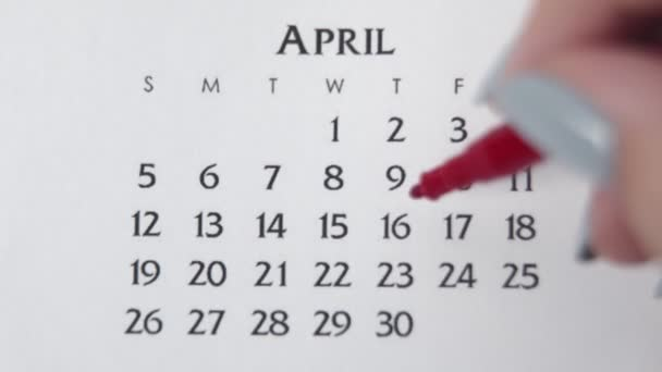 Female hand circle day in calendar date with a red marker. Business Basics Wall Calendar Planner and Organizer. APRIL 16th