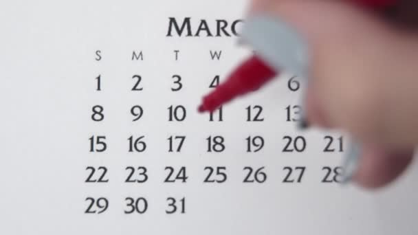 Female hand circle day in calendar date with a red marker. Business Basics Wall Calendar Planner and Organizer. MARCH 17th