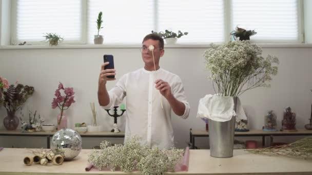 Mladý muž květinářství v brýlích se selfie s čerstvými květy v květinovém designu studio.