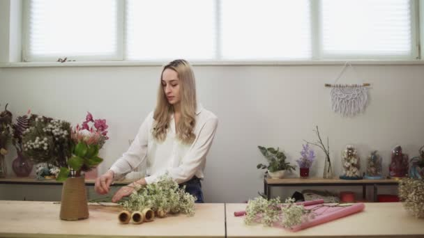 Floristin im Blumenladen. Frau macht einen schönen und stilvollen Strauß frischer Blumen im Floristikstudio.