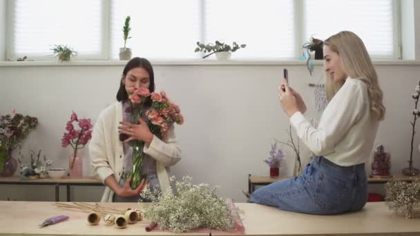 Young women takes photos with fresh flowers in shop