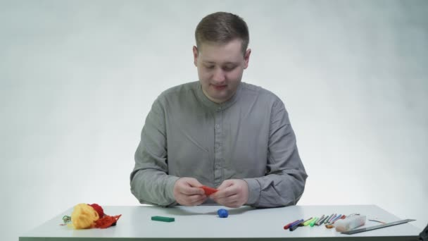 Young man makes something with plasticine at the table in a white studio