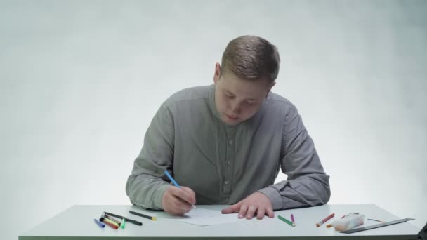 Young man uses colour pencils to draws a girls face on paper at the table in a white studio