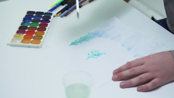 Close up of artist draws with watercolors on a white paper at the table in a white studio