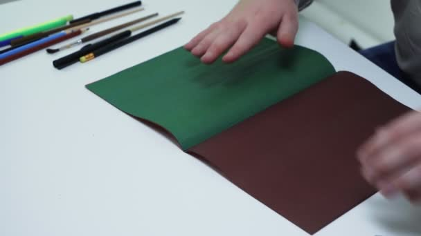Top nézet az ember használja ceruza és vonalzó felhívni vonalak egy zöld színű papírt az asztalnál egy fehér stúdió