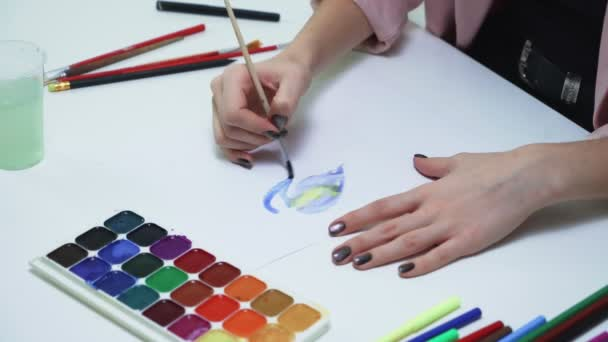 Close up of woman draws with watercolors on a white paper at the table in a white studio