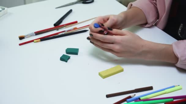 Top view of woman makes something with plasticine at the table