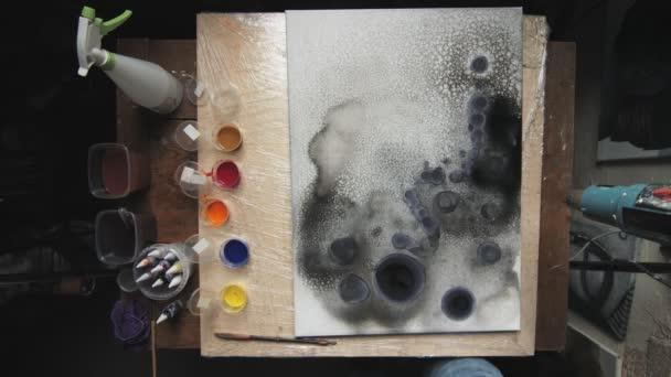 Fluide Kunst. Abstrakte dunkle Malerei. Draufsicht des männlichen Künstlers verwendet Trockner, um Farbe auf Leinwand zu trocknen