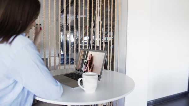 Junge brünette Frau spricht auf Videoanruf mit Freund mit Laptop-Computer in der heimischen Küche