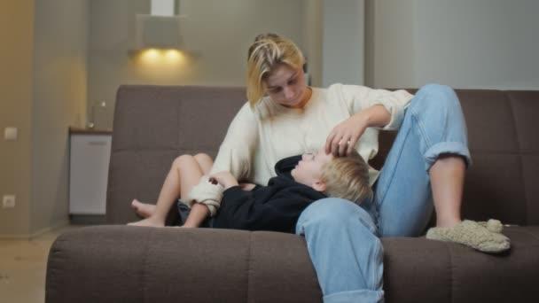 Glücklicher kleiner Junge in schwarzem Kapuzenpulli liegt mit seiner Mutter auf dem Sofa und spricht mit ihr