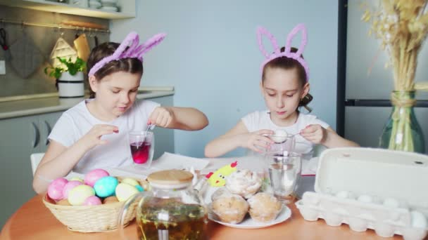 Little girls wearing bunny ears painting eggs on Easter day