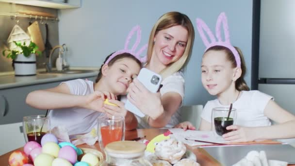 Happy family preparing for Easter. Cute little girls wearing bunny ears takes selfie photo on Easter day.