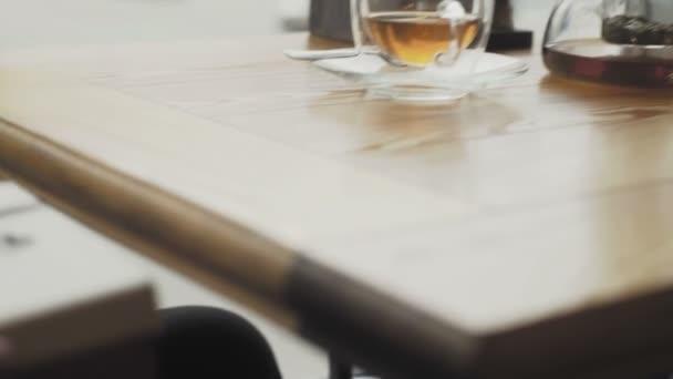 Muž vezme zpod stolu dárkovou krabici a položí ji na stůl v kavárně nebo restauraci.