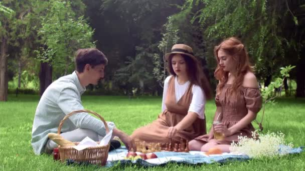A guy and two girls had a picnic and started playing chess in nature in the summer
