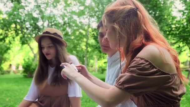 The girl shows her friends photos on the phone in nature in the summer