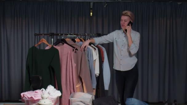 Mladá žena prodejce rozhovory se zákazníkem na telefonu a pracuje v second hand oblečení shop