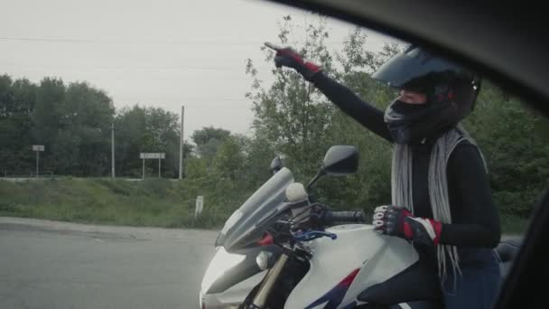 Young woman in a black helmet sits on motorbike and talks with car driver