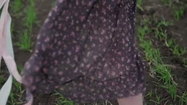 beautiful girl with ribbon in dark dress with floral print run across the green field and wind blowing her hair camera follow from shoes to hair close rear shot