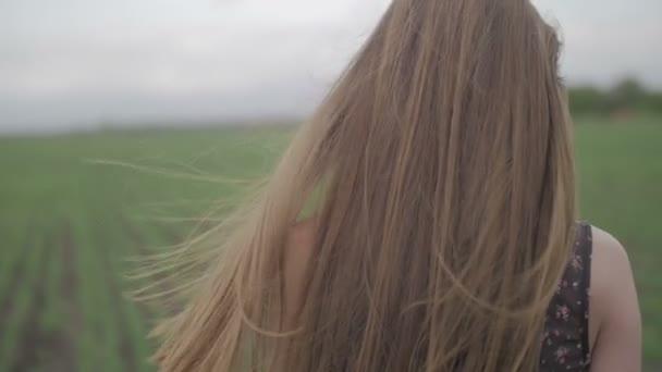 Krásná zdravá žena v tmavých šatech s květinovým potiskem stojí v a pak běží přes zelené pole ohlédnout a vítr fouká, vlasy jí zblízka netříděných plochý barevný