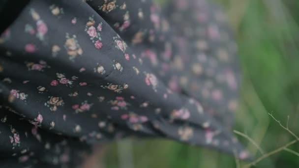 tmavé šaty s květinovým tisku vane vítr oblečený krásná žena blízko se zastřelil zelené pozadí