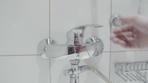 the man opens tap in white bathroom close up slow motion