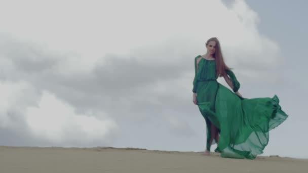 Lány zöld ruhában, a homok dűne, miközben a szél fúj a ruhát lassú mozgás ég háttér alakját lövés állni
