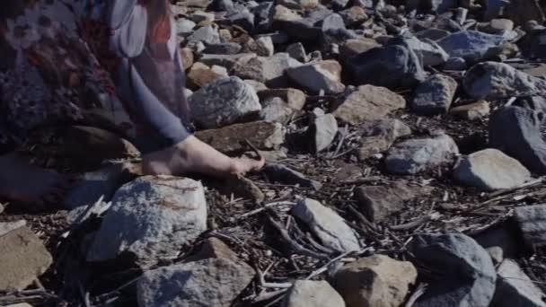 Zavřít detail Zenske nohy v dlouhé šaty, stojící na velké kameny s vozovkou