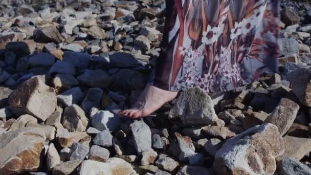 Zavřít detail Zenske nohy v dlouhých šatech, stojící na velké kameny