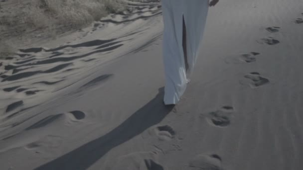 Feet of woman walking on beach dunes in white dress while sun drops shadow flat color