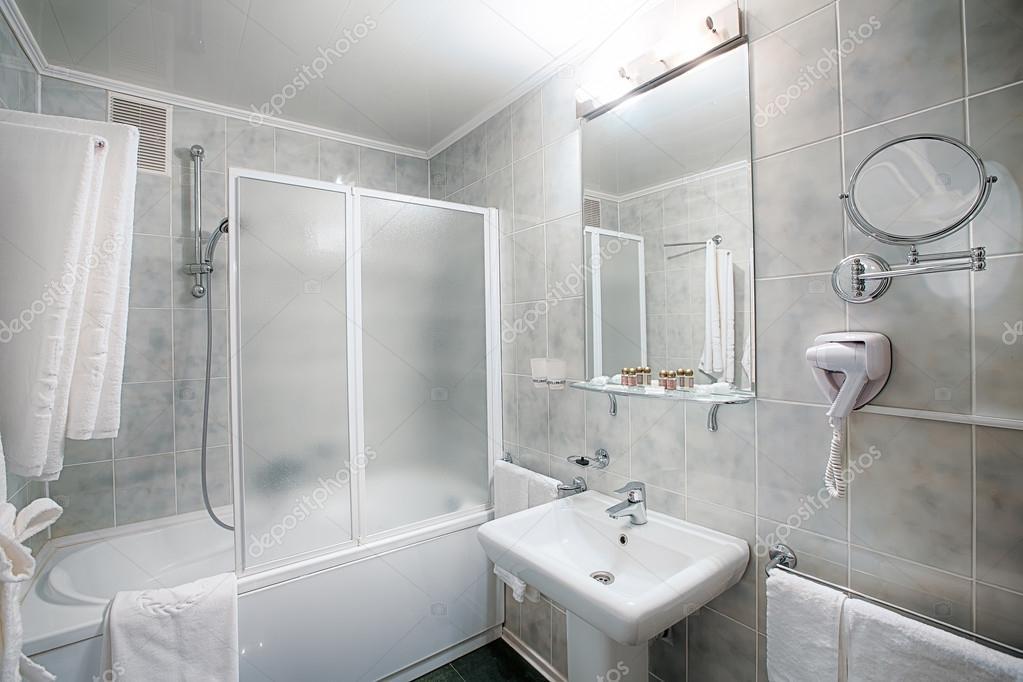 Moderne kleine badkamer met ligbad dubbele wastafel toilet en