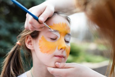 Child painting process at girls face