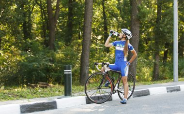 Female cyclist drinks water at the race, break