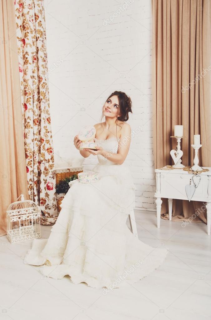 Junge Braut im Hochzeitskleid öffnet vorhanden — Stockfoto © Milkos ...