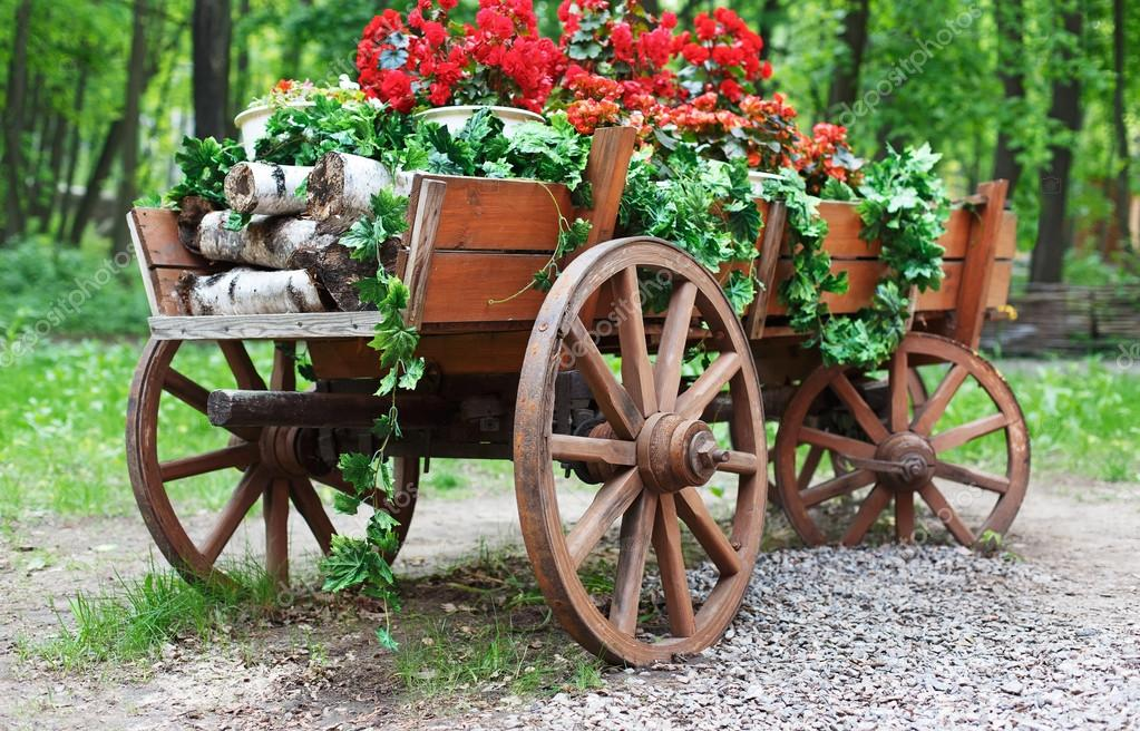 The cart with scarlet red geranium flowers in park