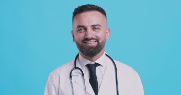 Studio portrét mužského lékaře středního věku, v bílém plášti, s úsměvem na kameru přes modré pozadí studia