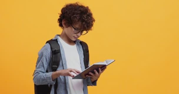 Stúdió portré koncentrált iskolás olvasókönyv, visel hátizsák és szemüveg, narancs háttér