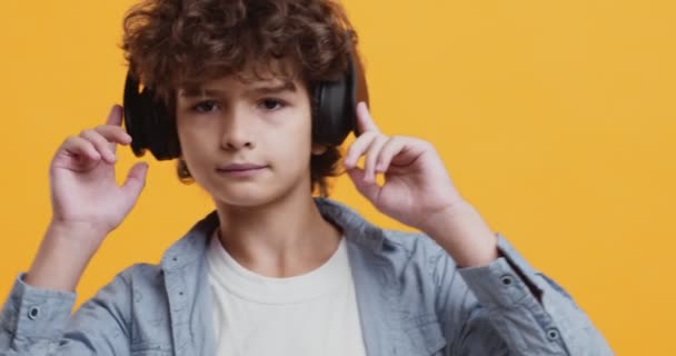 Little music lover. Cute boy listening music in headphones and dancing
