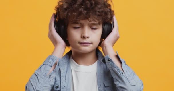 Close up studio portrét kudrnatý malý chlapec těší hudbu ve velkých bezdrátových sluchátkách