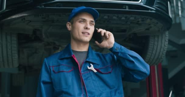 Junger Mechaniker telefoniert beim Wartungsservice mit Kunden über Autoschäden