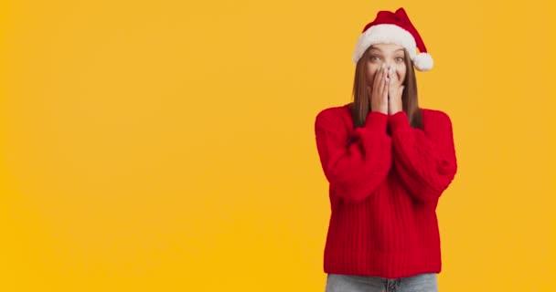 Nadšený tisíciletá dáma v červeném svetru a Santa klobouk těší sezónní nabídku, ukazuje na prázdném místě, oranžové pozadí