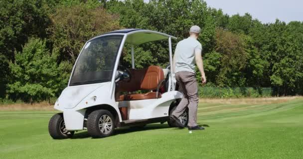 Mladý muž odchází od elektrického golfového auta, bere golfovou hůl zezadu a houpe s ní