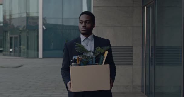 Depressed african american male office worker leaving business center building with box of personal stuff