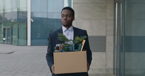Coronacrisis and unemployment. Sad african american manager going outdoors along office, holding box of personal staff