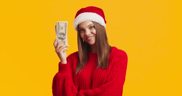 Young pleased lady in Santa hat holding stack of dollar banknotes, smiling over orange studio background