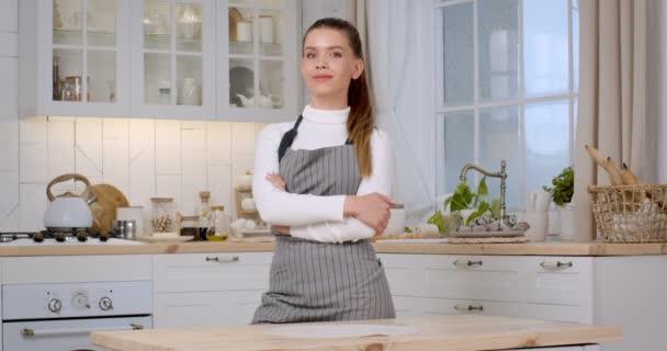 Usmívající se hezká žena v zástěře pózuje se založenýma rukama a dívá se na kameru v kuchyni
