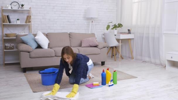 Mladá žena v gumových rukavicích mytí podlahy doma, pomocí pracích prostředků, zpomalení