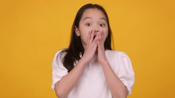 Shocked little asian girl feeling surprised, closing her mouth in amazement, orange background